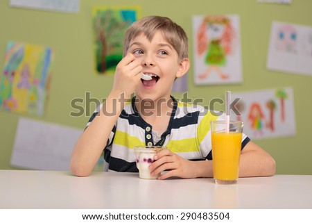 Happy child eating healthy snack and drinking orange juice