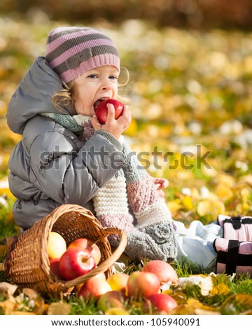 Happy child eating red apple in autumn park. Healthy lifestyles concept