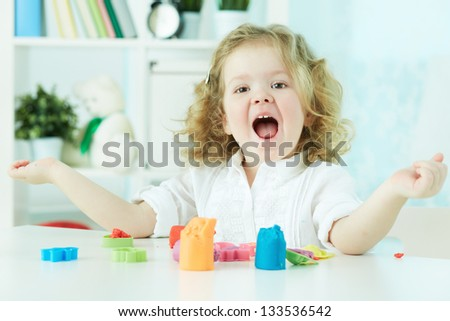 Happy child enjoying herself modeling with colorful clay