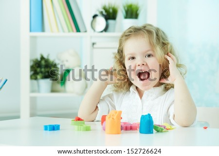 Happy child enjoying herself while modeling with colorful clay