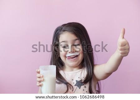 Happy child girl drinking yogurt. Whiskers from yogurt. - Shutterstock ID 1062686498