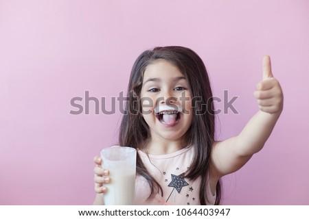 Happy child girl drinking yogurt. Whiskers from yogurt. - Shutterstock ID 1064403947