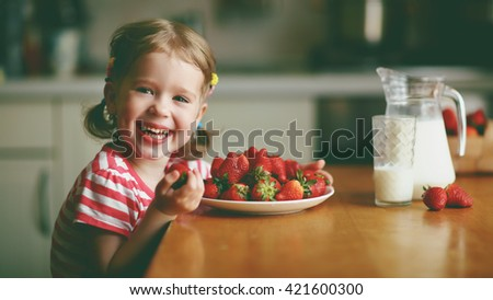 happy child girl drinks milk and eats strawberries in the summer home kitchen