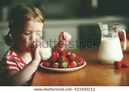 happy child girl drinks milk and eats strawberries in the summer home kitchen #421600312