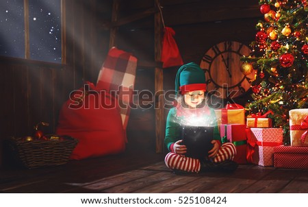 Stock Photo happy child girl elf helper of Santa with a magic Christmas gift