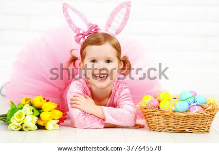 Happy child girl in a costume Easter bunny rabbit with basket of eggs and flowers tulips #377645578