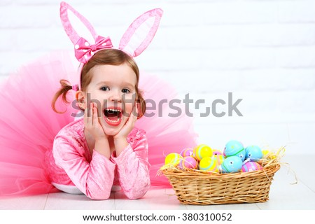 Happy child girl in a costume Easter bunny rabbit with ears and a basket of eggs #380310052