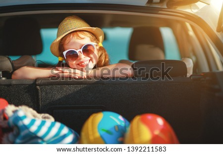 happy child girl in car going on a summer vacation trip Foto stock ©
