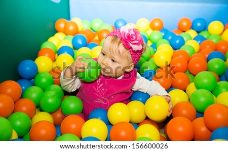 Happy child girl in colored ball on playground  The concept of childhood and holiday