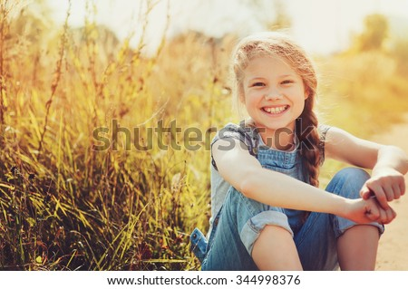 happy child girl in jeans overall playing on sunny field, summer outdoor lifestyle, cozy mood