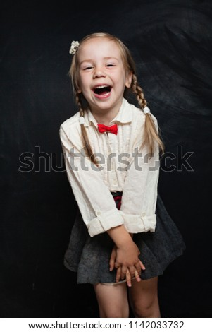 16fb05b1d684 Happy child girl in school uniform having fun and laughing on chalk board  background. Back