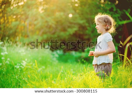 happy child girl in white shirt dreaming on the walk on summer field