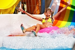 Happy child girl in yellow bikini sliding water park.