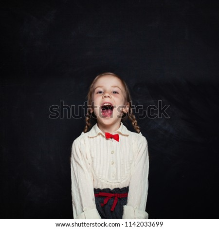 Happy child girl laughing and having fun. Smiling kid in school uniform on empty blackboard background with copy space. Back to school. #1142033699