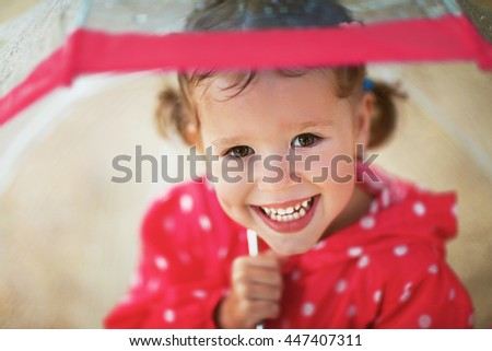 happy child girl laughing with an umbrella in the rain #447407311