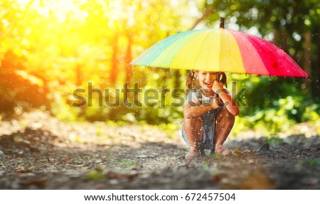 Happy child girl laughs and plays under the summer rain with an umbrella #672457504