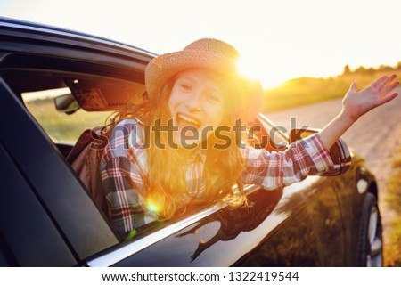 happy child girl looking out the car window during road trip on summer vacations. Summertime, exploring new places concept #1322419544