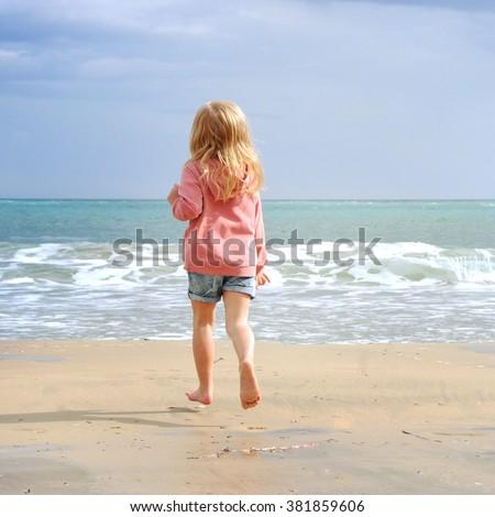 Happy child girl on a sea beach #381859606