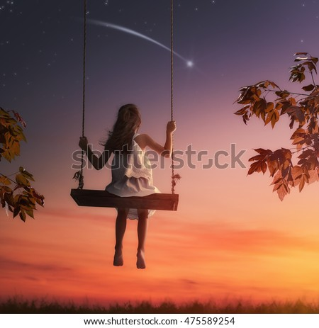 Happy child girl on swing in sunset summer. Kid makes a wish by seeing a shooting star.