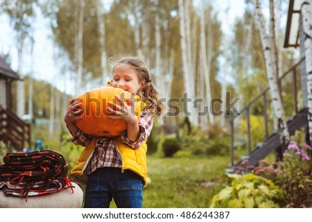 happy child girl picking fresh pumpkins on the farm. Country living concept, growing vegetables on farm #486244387