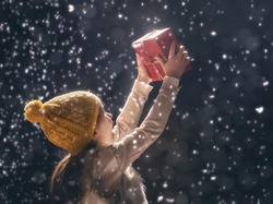Happy child girl playing on a snowy winter walk. Little girl enjoys the game. Child girl playing outdoors in snow. Outdoor fun for winter vacation. Portrait kid with gift box on dark background.