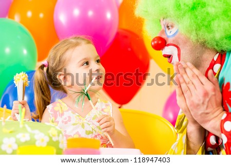 happy child girl playing with clown on birthday party