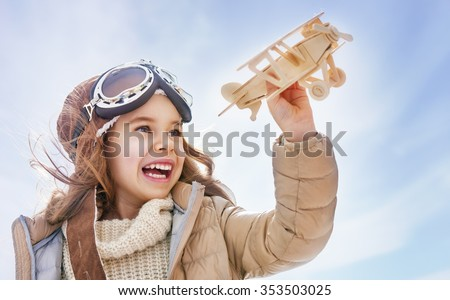 Stock Photo happy child girl playing with toy airplane. the dream of becoming a pilot
