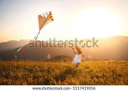 happy child girl running with a kite at sunset outdoors ストックフォト ©