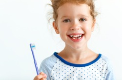 happy child girl with toothbrush brushes teeth and smiles
