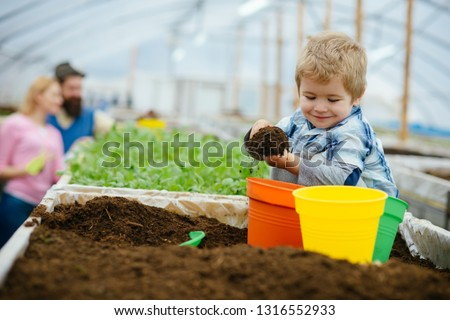 happy child. happy child workign with soil in garden. happy child in greenhouse. happy child with family in farm. enjoying his work with plants