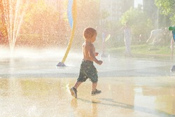 Happy child has fun playing in water fountains on hot day during summer. Boy playing in water at waterpark. A kid in spray park.