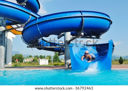 happy child have fun on water slike on outdoor swimming pool