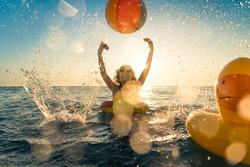Happy child having fun on summer vacation. Kid playing with rubber duck and ball in the sea. Healthy lifestyle concept. Spring break!