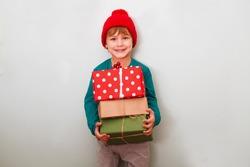 Happy child holding big Christmas presents. Christmas time.