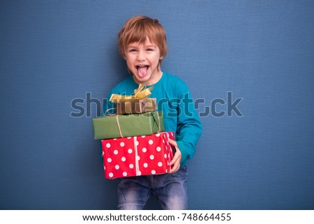 Stock Photo Happy child holding Christmas presents on a blue background. Christmas time. Children's birthday.