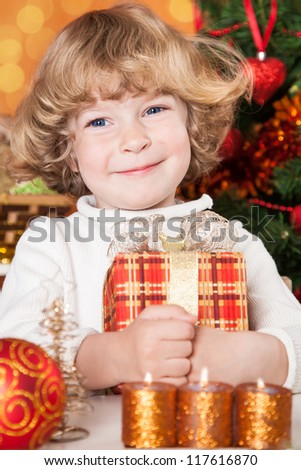 Happy child holding gift box against Christmas tree with decorations