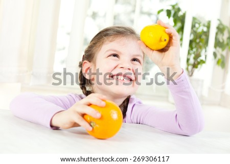 Happy child holding orange and lemon