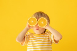 Happy child holding orange. Portrait of funny kid against yellow background