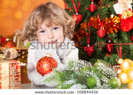 Happy child holding red ball against Christmas tree with decorations