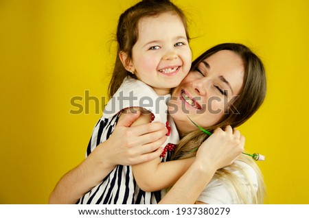 Happy child hugs mom. Strong hugs for children. Little daughter hugs mom. Happy mother with her baby on a yellow background. Hugs of mom and baby on a yellow background. A loving family.Family concept