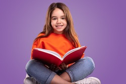 Happy child in casual clothes smiling and looking at camera while sitting crossed legged against violet background and reading book during school lesson