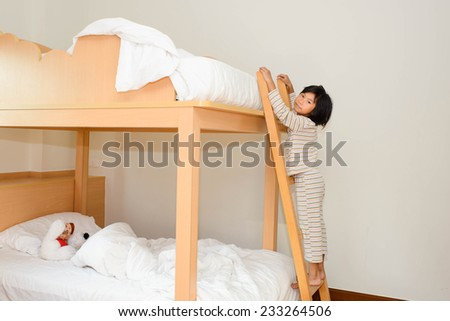 Happy child in child\'s room on a bunk-beds