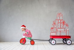 Happy child in Christmas time. Funny kid playing at home. Xmas winter holiday concept
