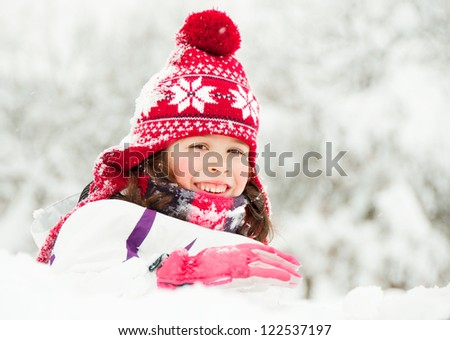 Happy child in red hat on snow