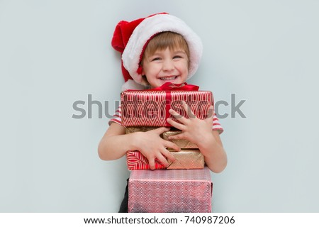 Happy child in Santa red hat holding Christmas presents. Christmas time.
