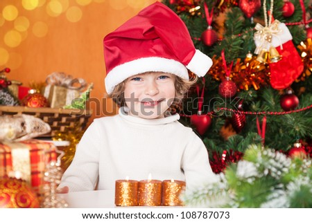 Happy child in Santa`s hat against Christmas tree with decorations