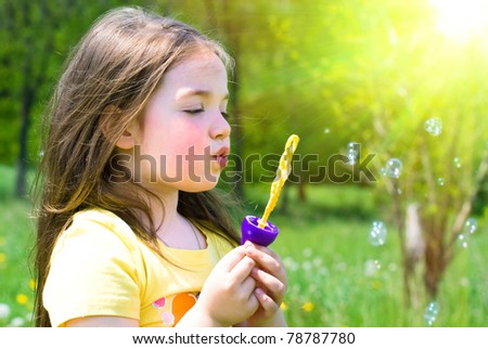 Happy Child in Summer.  Beautiful Girl blows Bubbles. Happy Children. Healthy Kids. Spring Time. Vacation in the Countryside.