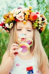 Happy Child in Summer.  Beautiful Girl with Flowers Wreath from Flowers blows Soap Bubbles. Happy Children. Healthy Kids. Spring Time.