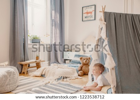 Happy child in tent playing in bedroom interior with plush toy and fox poster above bed. Real photo