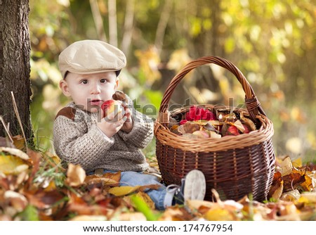 Happy child in warm clothes is playing in colorful autumn nature